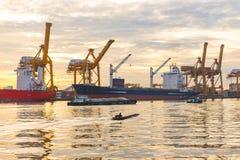 Η μακριά βάρκα ουρών ψαράδων και το σκάφος φορτίου φορτίου εμπορευματοκιβωτίων σκιαγραφούν το πρωί Στοκ Φωτογραφίες