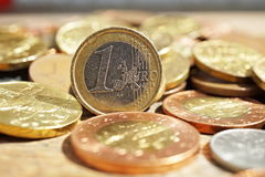 Η μακρο λεπτομέρεια ενός σωρού των νομισμάτων στην ξύλινη επιφάνεια με ένα ασημένιο και χρυσό ευρο- νόμισμα χώρισε από άλλο μεταλ Στοκ Εικόνες