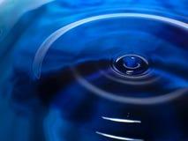 Η μακρο φωτογραφία μιας σκούρο μπλε πτώσης/ενός μελανιού νερού ρίχνει τον παφλασμό και τους κυματισμούς, υγρός, εννοιολογικούς γι Στοκ Φωτογραφίες