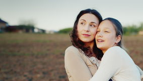 Η μαμά αγκαλιάζει ήπια την κόρη της για 11 έτη Μαζί κοιτάζουν σε μια κατεύθυνση στον ήλιο ρύθμισης Οικογενειακές αξίες φιλμ μικρού μήκους