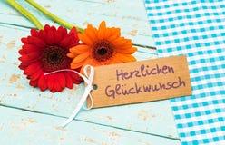 Η μαργαρίτα Gerbera ανθίζει με τη ευχετήρια κάρτα και το γερμανικό κείμενο, Herzlichen Glueckwunsch, συγχαρητήρια μέσων στοκ εικόνα με δικαίωμα ελεύθερης χρήσης