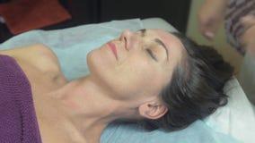 Η μασέρ κάνει το μασάζ του κεφαλιού στη γυναίκα στην επαγγελματική αίθουσα Σχετικά με το τρίχωμα απόθεμα βίντεο