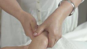 Η μασέρ κάνει το μασάζ των δεξιών δάχτυλων στην ενήλικη γυναίκα στην αίθουσα ομορφιάς φιλμ μικρού μήκους