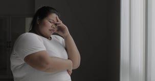 Η ματαιωμένη υπέρβαρη γυναίκα στέκεται κοντά στο παράθυρο φιλμ μικρού μήκους