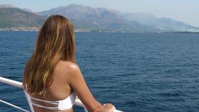 Η μαυρισμένη νέα γυναίκα στέκεται στο σκάφος και παρατηρεί τη θάλασσα απόθεμα βίντεο