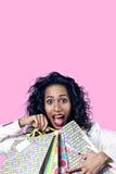 Η μαύρη γυναίκα ευχαριστημένη από τις τέλειες τσάντες εγγράφου αγορών, άνοιξε το στόμα Στοκ Εικόνες
