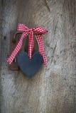 Η μαύρη καρδιά με μια κόκκινη άσπρη ελεγχμένη κορδέλλα που κρεμά σε έναν παλαιό Στοκ εικόνες με δικαίωμα ελεύθερης χρήσης