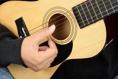 η μαύρη κιθάρα ανασκόπησης δίνει στον ώμο φορέων παιχνιδιού φωτογραφιών του τη στερεά κατακόρυφο Στοκ Εικόνες