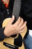 η μαύρη κιθάρα ανασκόπησης δίνει στον ώμο φορέων παιχνιδιού φωτογραφιών του τη στερεά κατακόρυφο Στοκ Φωτογραφίες