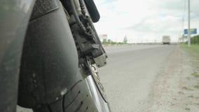 Η μαύρη να περιοδεύσει μοτοσικλέτα στέκεται στο πεζοδρόμιο Κατώτατη άποψη από την μπροστινή ρόδα στον μπροστινό δρόμο απόθεμα βίντεο