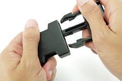 Η μαύρη πλαστική πόρπη κλειδαριών κλειδώνεται και από τα δύο χέρια στο άσπρο backg Στοκ Εικόνες