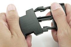 Η μαύρη πλαστική πόρπη κλειδαριών κλειδώνεται και από τα δύο χέρια στο άσπρο backg Στοκ φωτογραφία με δικαίωμα ελεύθερης χρήσης