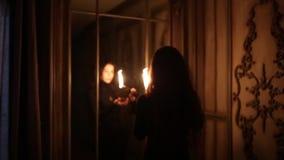 Η μαύρος-μαλλιαρή μάγισσα ανάβει ένα κερί και στέκεται κοντά στον καθρέφτη στο σκοτάδι φιλμ μικρού μήκους
