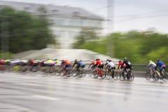 Η μεγάλη ομάδα ζωηρόχρωμων συναγωνιμένος ποδηλατών στην οδό πόλεων, ημέρα, περίληψη, αθλητική κίνηση θόλωσε το υπόβαθρο με το διά Στοκ Εικόνες
