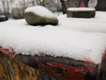 Η μεγάλη πέτρα που συνεδρίαση στο χάλυβα κάτω από το χιόνι Στοκ Φωτογραφίες