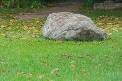 Η μεγάλη ασημένια πέτρα στην πράσινη χλόη περιέβαλε τα φύλλα φθινοπώρου Στοκ φωτογραφία με δικαίωμα ελεύθερης χρήσης