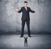 Η μεγάλη επιχείρηση φοβερίζει την εξέταση το μικρό συνάδελφο Στοκ Εικόνα