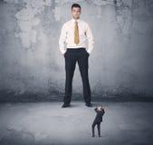Η μεγάλη επιχείρηση φοβερίζει την εξέταση το μικρό συνάδελφο Στοκ φωτογραφία με δικαίωμα ελεύθερης χρήσης