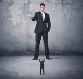 Η μεγάλη επιχείρηση φοβερίζει την εξέταση το μικρό συνάδελφο Στοκ Εικόνες