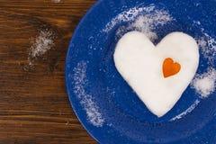 Η μεγάλη καρδιά χιονιού που διακοσμείται με τη μικρή πορτοκαλιά καρδιά που βρίσκεται στο μπλε πιάτο στοκ φωτογραφία με δικαίωμα ελεύθερης χρήσης