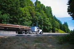 Η μεγάλη οδηγώντας εθνική οδός φορτηγών εγκαταστάσεων γεώτρησης ημι φέρνει τους μακριούς σωλήνες στο επίπεδο κρεβάτι Στοκ Φωτογραφία