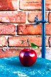Η μεγάλη ώριμη κόκκινη Apple με τα πράσινα φύλλα στον εκλεκτής ποιότητας ξύλινο πίνακα. Φ Στοκ Εικόνες