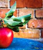 Η μεγάλη ώριμη κόκκινη Apple με τα πράσινα φύλλα στον εκλεκτής ποιότητας ξύλινο πίνακα. Φ Στοκ εικόνες με δικαίωμα ελεύθερης χρήσης