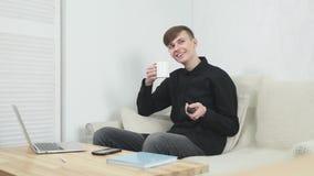 Η μεγάλη TV παρουσιάζει Όμορφος εύθυμος νεαρός άνδρας που κρατά τον τηλεχειρισμό και που προσέχει τη TV καθμένος στον καναπέ στο  απόθεμα βίντεο