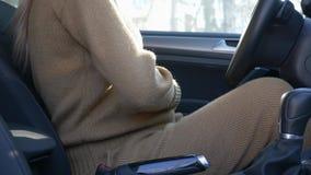 Η μελλοντική μητέρα ανοίγει την πόρτα και παίρνει στο αυτοκίνητο, το κορίτσι που κτυπά μεγάλο tummy της και βάζει έπειτα στη ζώνη απόθεμα βίντεο