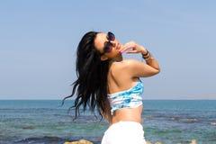 Η μελαχροινή μαλλιαρή γυναίκα με τα γυαλιά ηλίου και beachwear απολαμβάνει τον ήλιο στοκ εικόνες με δικαίωμα ελεύθερης χρήσης