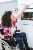 Η με ειδικές ανάγκες νέα γυναίκα στην αναπηρική καρέκλα ανοίγει το φούρνο Στοκ Εικόνες