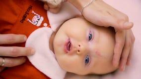 Η μητέρα αγγίζει ήπια το νεογέννητο κορίτσι στο κόκκινο φόρεμα απόθεμα βίντεο