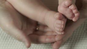 Η μητέρα αγγίζει και κτυπά τα πόδια μωρών απόθεμα βίντεο