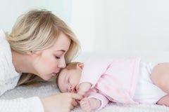 Η μητέρα βάζει την κόρη μωρών της στον ύπνο Στοκ φωτογραφία με δικαίωμα ελεύθερης χρήσης