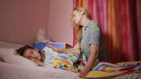 Η μητέρα βάζει την κόρη στο κρεβάτι απόθεμα βίντεο