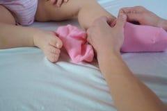 Η μητέρα βάζει τις ρόδινες κάλτσες στα πόδια μωρών ` s στο κρεβάτι Στοκ Φωτογραφία