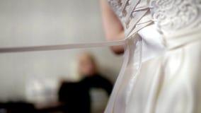 Η μητέρα βοηθά τη νύφη για να βάλει σε ένα γαμήλιο φόρεμα Απόθεμα Τα χέρια δένουν έναν κορσέ ενός γαμήλιου φορέματος απόθεμα βίντεο