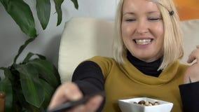 Η μητέρα για να είναι τρώει το πρόχειρο φαγητό και γελά έξω δυνατός προσέχοντας την τηλεόραση απόθεμα βίντεο