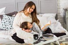 Η μητέρα διαβάζει ένα βιβλίο στην κόρη της στη ημέρα των Χριστουγέννων Στοκ φωτογραφία με δικαίωμα ελεύθερης χρήσης