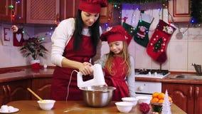 Η μητέρα διδάσκει την κόρη της που αναμιγνύει τα συστατικά με τον ηλεκτρικό αναμίκτη απόθεμα βίντεο