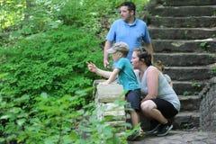 Η μητέρα επισημαίνει κάποια άγρια φύση ενώ strolling μέσω των ξύλων στοκ εικόνες