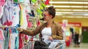 Η μητέρα επιλέγει τα ενδύματα για το παιδί τους στην αγορά, το κορίτσι στέκεται κοντά στο ράφι υπεραγορών και επιλέγει το σώμα γι απόθεμα βίντεο