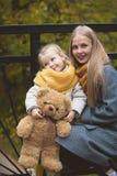 Η μητέρα, η κόρη και το παιχνίδι της Teddy αντέχουν και περπατώντας στο πάρκο φθινοπώρου, κλείστε επάνω Στοκ Φωτογραφίες