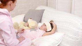 Η μητέρα θεραπεύει την κόρη παιδιών, το παιδί βρίσκεται στο κρεβάτι απόθεμα βίντεο