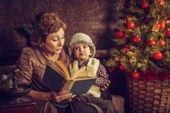 Η μητέρα διαβάζει στο γιο του το βιβλίο κοντά σε ένα χριστουγεννιάτικο δέντρο Στοκ Φωτογραφία