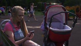 Η μητέρα κάθεται στον πάγκο στη βρύση παιδικών χαρών στο smartphone Κόκκινη μεταφορά μωρών Παιδιά φιλμ μικρού μήκους