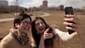 Η μητέρα και η ενήλικη κόρη παίρνουν selfies στο πάρκο το καλοκαίρι πηγαίνουν τρελλές και γελούν Ευτυχείς και θετικές συγκινήσεις φιλμ μικρού μήκους
