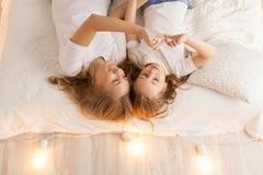 Η μητέρα και η κόρη βάζουν στο κρεβάτι και κάνουν την καρδιά με το χέρι επάνω από την όψη ενότητα εσωτερική σοφίτα σχεδίου σύγχρο Στοκ εικόνα με δικαίωμα ελεύθερης χρήσης
