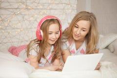 Η μητέρα και η κόρη βάζουν στο κρεβάτι στις πυτζάμες διδάσκουν και έχουν τη διασκέδαση, χρησιμοποιούν το lap-top και ακούνε μουσι Στοκ φωτογραφίες με δικαίωμα ελεύθερης χρήσης