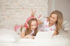 Η μητέρα και η κόρη βάζουν στο κρεβάτι στις πυτζάμες και έχουν τη διασκέδαση, χρησιμοποιούν το lap-top και ακούνε μουσική από τα  Στοκ φωτογραφία με δικαίωμα ελεύθερης χρήσης
